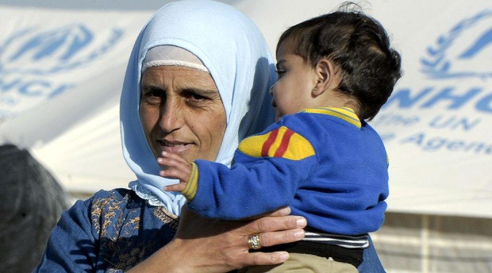 En syrisk kvinne med barn på armen, i den FN-drevne flyktingleiren Za'atri i Jordan. Fotograf: Mark Garten/FN
