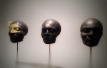 """Utsnitt av """"Tre hoder"""", 1972, Bård Breivik (1948–2016). Skulptur i bly, bladgull og fjær, samlet høyde: 170 centimeter."""